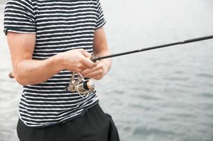 Sweden, Bohuslan, Tjorn, Mid section of young man fishingの写真素材 [FYI02701267]
