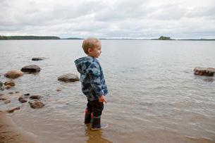 Finland, Punkaharju, Savolax, Boy (4-5) in rubber boots stanの写真素材 [FYI02701287]