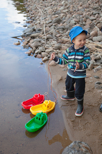 Finland, Punkaharju, Boy (4-5) playing on lakeshoreの写真素材 [FYI02701297]