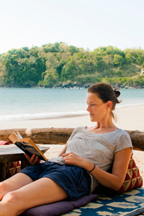Thailand, Koh Lanta, Woman reading on beachの写真素材 [FYI02701305]