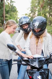 Sweden, Sodermanland, Nacka, Three girls (14-15) with motor scooterの写真素材 [FYI02701310]