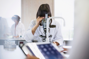 Female college student using microscope in science laboratory classroomの写真素材 [FYI02701416]