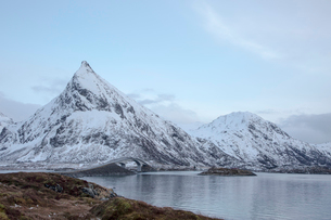 Snow covered mountains along cold lake, Lofoten Islands, Norwayの写真素材 [FYI02701453]