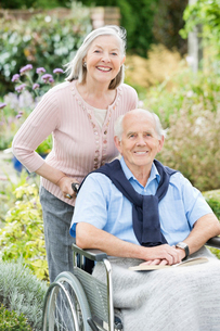 Older woman pushing husband's wheelchair outdoorsの写真素材 [FYI02701504]