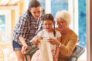 Grandmother teaching granddaughter knittingの写真素材 [FYI02701613]