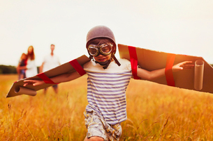Boy with wings in aviator's cap and flying goggles in fieldの写真素材 [FYI02701652]