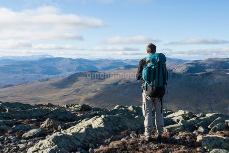 Sweden, Vasterbotten, Hemavan, Hiker looking at mountain landscapeの写真素材 [FYI02701656]