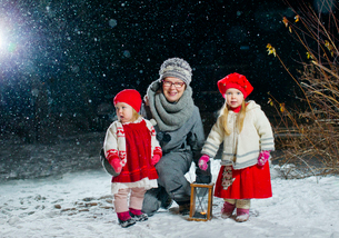 Finland, Portrait of grandmother with granddaughters (12-17 months, 2-3) in backyard at nightの写真素材 [FYI02701661]