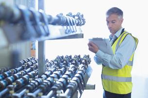 Engineer with clipboard checking printing press conveyor beltの写真素材 [FYI02701694]