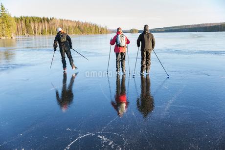 Sweden, Gastrikland, Edsken, Mature people ice skating on frozen lakeの写真素材 [FYI02701715]