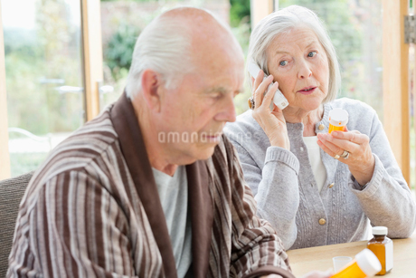 Older woman with medications talking on phoneの写真素材 [FYI02701722]