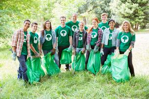 Portrait of smiling environmentalist volunteers picking up trashの写真素材 [FYI02701727]