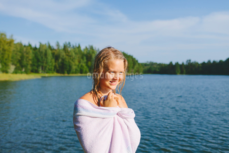 Finland, Pirkanmaa, Salmentaka, Lake Palkanevesi, Woman wrapped in towel at lakeの写真素材 [FYI02701759]