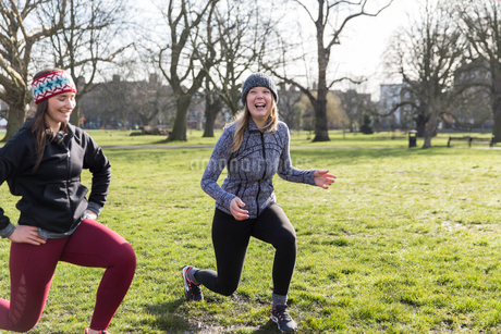 Smiling, confident women doing lunges in sunny parkの写真素材 [FYI02701855]