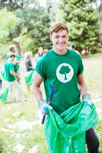 Portrait of smiling environmentalist volunteer picking up trashの写真素材 [FYI02701890]