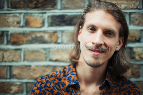 Portrait smiling, confident young male hipster with mustacheの写真素材 [FYI02701910]