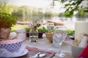 Place settings and simple bouquet on garden party table at lakesideの写真素材 [FYI02701914]
