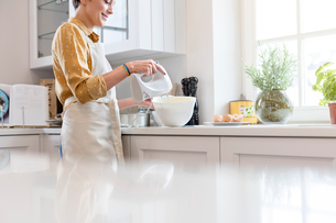 Woman baking, using electric hand mixer in kitchenの写真素材 [FYI02701919]