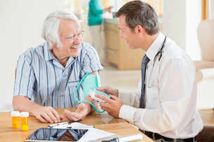 Doctor testing older patient's blood pressure at house callの写真素材 [FYI02701935]