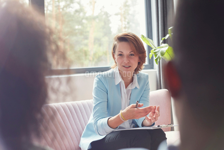 Female therapist talking to couple in couples therapy sessionの写真素材 [FYI02701947]