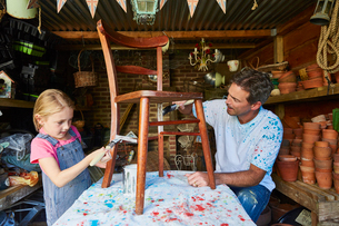 Father and daughter painting chair in workshopの写真素材 [FYI02702009]