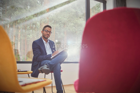 Portrait confident businessman writing on clipboard in officeの写真素材 [FYI02702027]