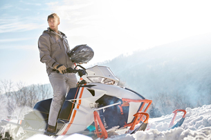 Man riding snowmobile in sunny snowy fieldの写真素材 [FYI02702094]