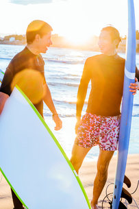 Male surfers with surfboards talking on sunny ocean beachの写真素材 [FYI02702148]