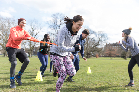 People racing, doing team building exercise in sunny parkの写真素材 [FYI02702178]