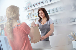 Female business owner giving shopping bag to shopper in art paint shopの写真素材 [FYI02702190]