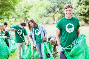 Portrait of smiling environmentalist volunteer picking up trashの写真素材 [FYI02702227]