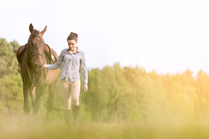 Woman walking horse in rural fieldの写真素材 [FYI02702285]