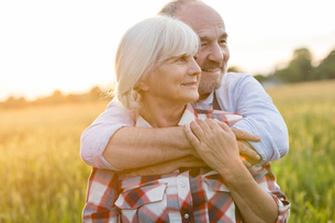 Senior couple hugging in rural wheat fieldの写真素材 [FYI02702287]