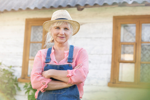 Portrait smiling farmer in overalls and straw hat outside farmhouseの写真素材 [FYI02702322]
