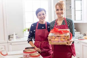 Portrait smiling female caterers showing wrapped box of pastries in kitchenの写真素材 [FYI02702354]