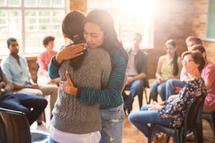 Women hugging in group therapy sessionの写真素材 [FYI02702356]