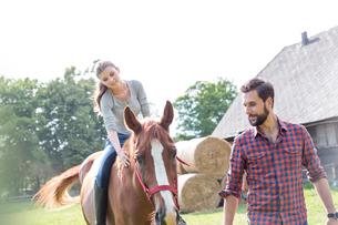 Man leading woman horseback riding in rural pastureの写真素材 [FYI02702409]