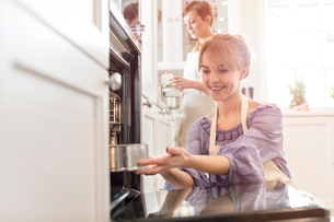 Smiling woman baking, placing cake in ovenの写真素材 [FYI02702418]
