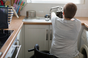 Young woman in wheelchair filling kettle for tea at apartment kitchen sinkの写真素材 [FYI02702442]