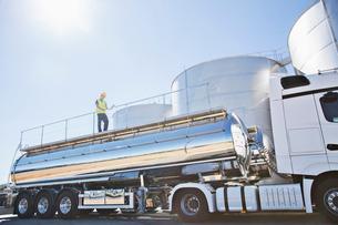 Worker on platform above stainless still milk tankerの写真素材 [FYI02702474]