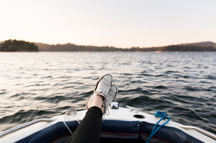 Personal perspective woman boating with feet up on tranquil lakeの写真素材 [FYI02702475]