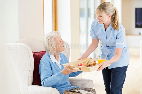Caregiver giving older woman tray of foodの写真素材 [FYI02702518]