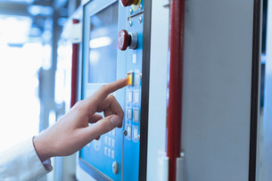 Close up of worker at control panel in factoryの写真素材 [FYI02702526]