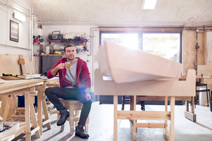 Male carpenter drinking tea next to wood boat in workshopの写真素材 [FYI02702530]