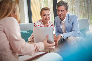 Therapist showing digital tablet to couple in couples therapy counseling sessionの写真素材 [FYI02702564]