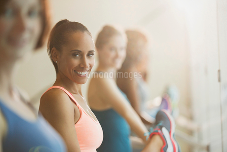 Portrait smiling women stretching legs at barre in exercise class gym studioの写真素材 [FYI02702590]