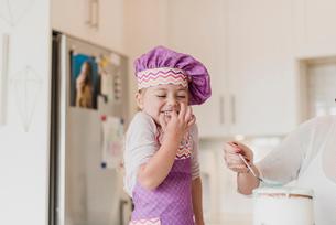 Happy, cute girl in chef?s hat baking in kitchenの写真素材 [FYI02702612]