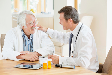 Doctor talking to older patient at house callの写真素材 [FYI02702657]