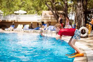 Turkey, Mugla, Marmaris, Boy (6-7) wearing diving slippers jumping into swimming pool at holiday resの写真素材 [FYI02702677]