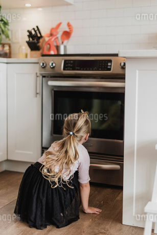 Curious girl watching ovenの写真素材 [FYI02702687]
